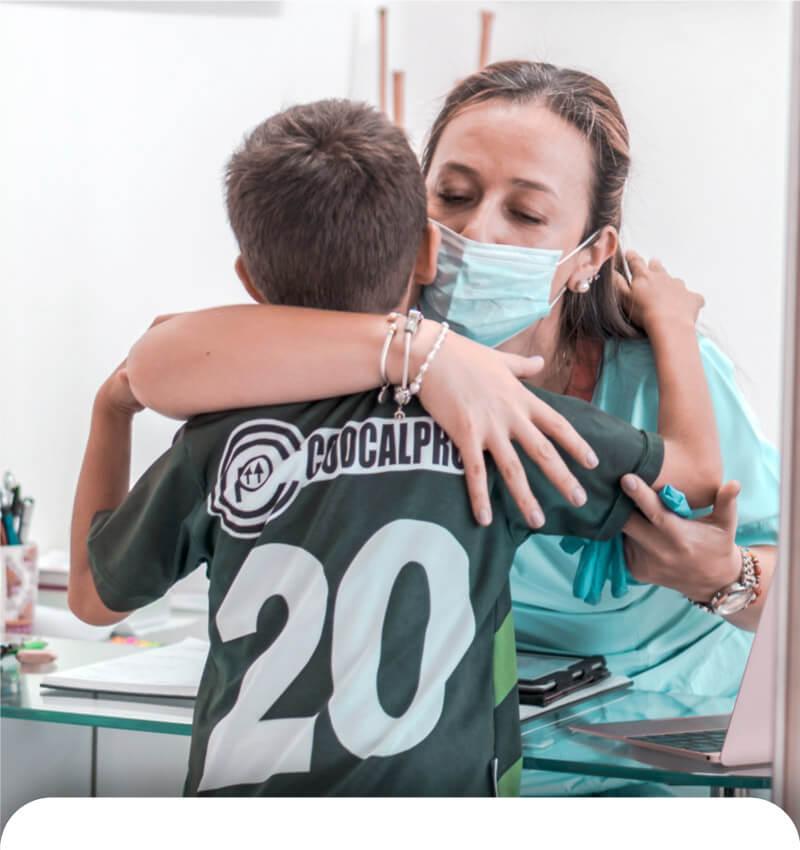 Odontologa abrazando paciente en consultorio